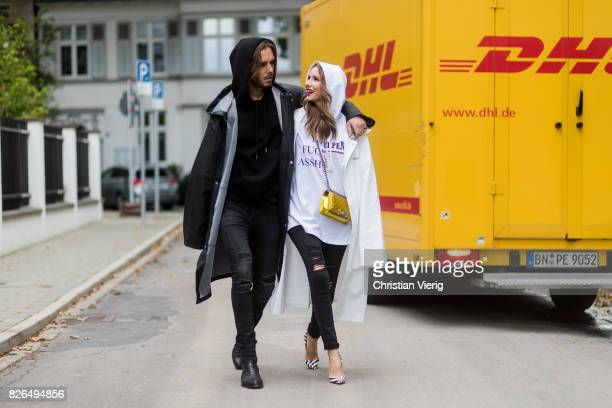 Couple look a like holding arms in front of a DHL van Model and Blogger Alexandra Lapp wearing oversized raincoat with a hood in white from Vetements...