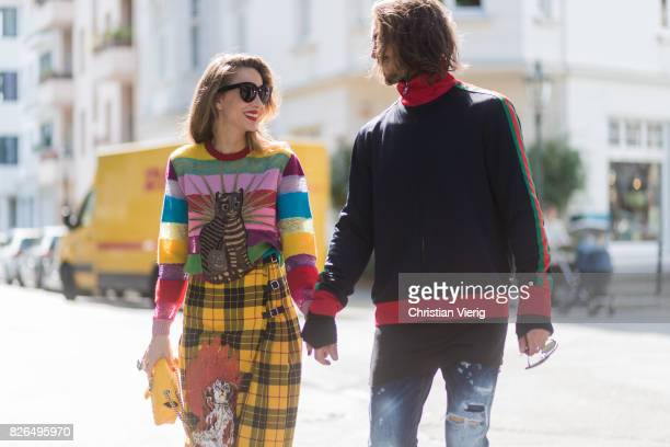 Couple look a like holding hands in front of DHL van Model and Blogger Alexandra Lapp wearing a yellow and red pleated tartan skirt embroidered with...
