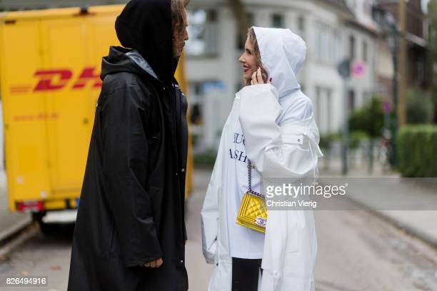 Couple look a like talking in front of a DHL van Model and Blogger Alexandra Lapp wearing oversized raincoat with a hood in white from Vetements...