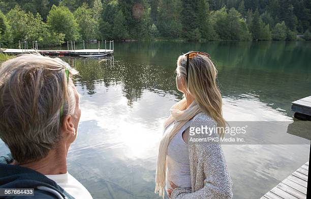 Couple look across forest pond from pier, content