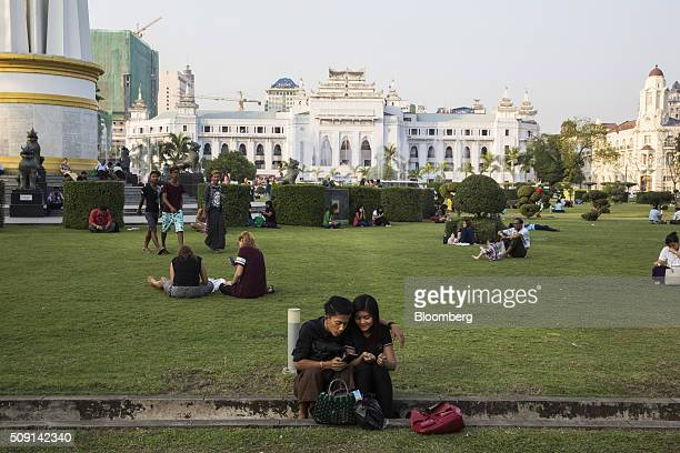 A couple look at a mobile device while other visitors and tourists sit in Maha Bandoola Garden as Yangon City Hall stands in the background in Yangon...