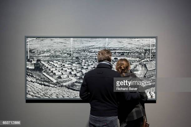 A couple look at a stills picture from the documentary artwork entitled 'Incoming' by Richard Mosse on 5th March 2017 at the Barbican in the City of...