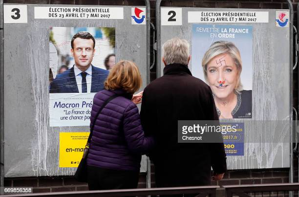 A couple look at graffitied official campaign posters of Marine Le Pen French National Front and political party leader and Emmanuel Macron head of...