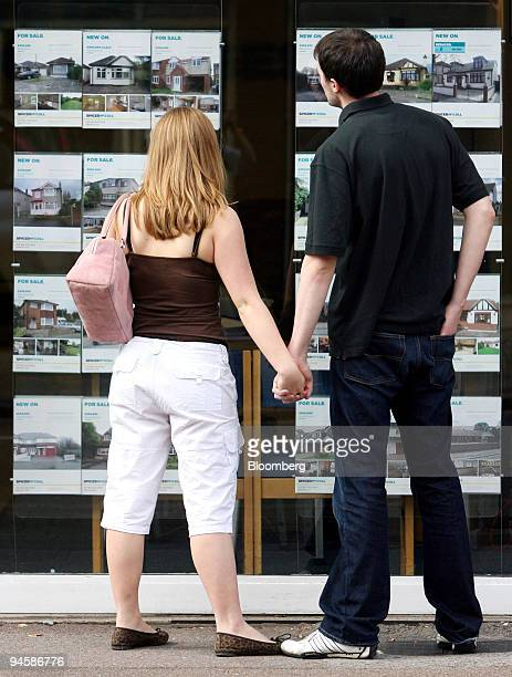 A couple look at houses displayed for sale in an estate agents window in Hornchurch Essex UK on Thursday Sept 13 2007 UK house prices fell for the...