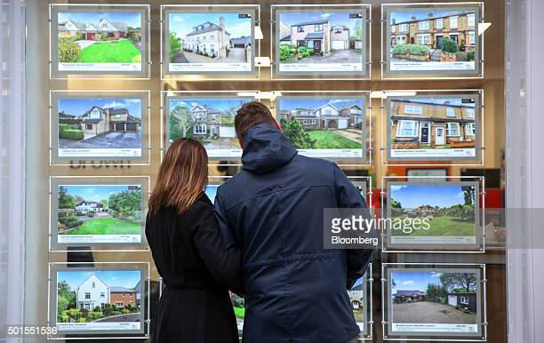A couple look at houses for sale in the window of William H Brown estate agents in this arranged photograph in Chelmsford UK on Tuesday Dec 15 2015...