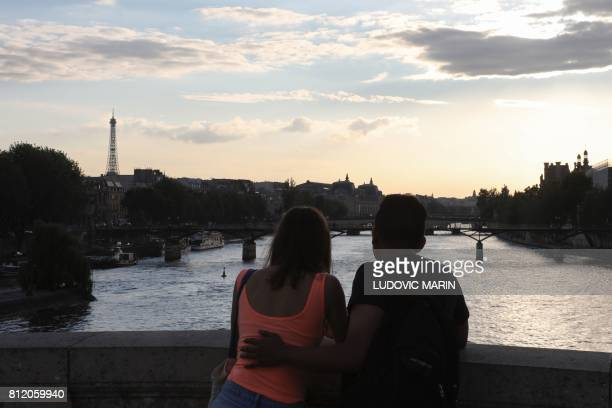 A couple look at the Eiffel Tower in fronf of the Seine river from the Pont Neuf bridge in Paris on July 10 2017 / AFP PHOTO / ludovic MARIN