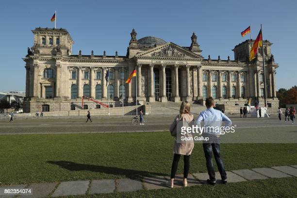 A couple look at the Reichstag seat of the Bundestag on October 17 2017 in Berlin Germany Following German federal elections last September the new...