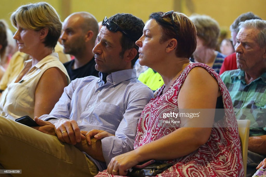 A couple look on during an afternoon community meeting to advise residents of the current fire situation at the Brown Park community centre on January 13, 2014 in Perth, Australia. Evacuated residents of Perth Hills are awaiting permission to access and inspect their properties after a bushfire blazed through the suburb, destroying over 46 homes. Emergency services are assessing the affected area and expected the number of properties damaged to increase.