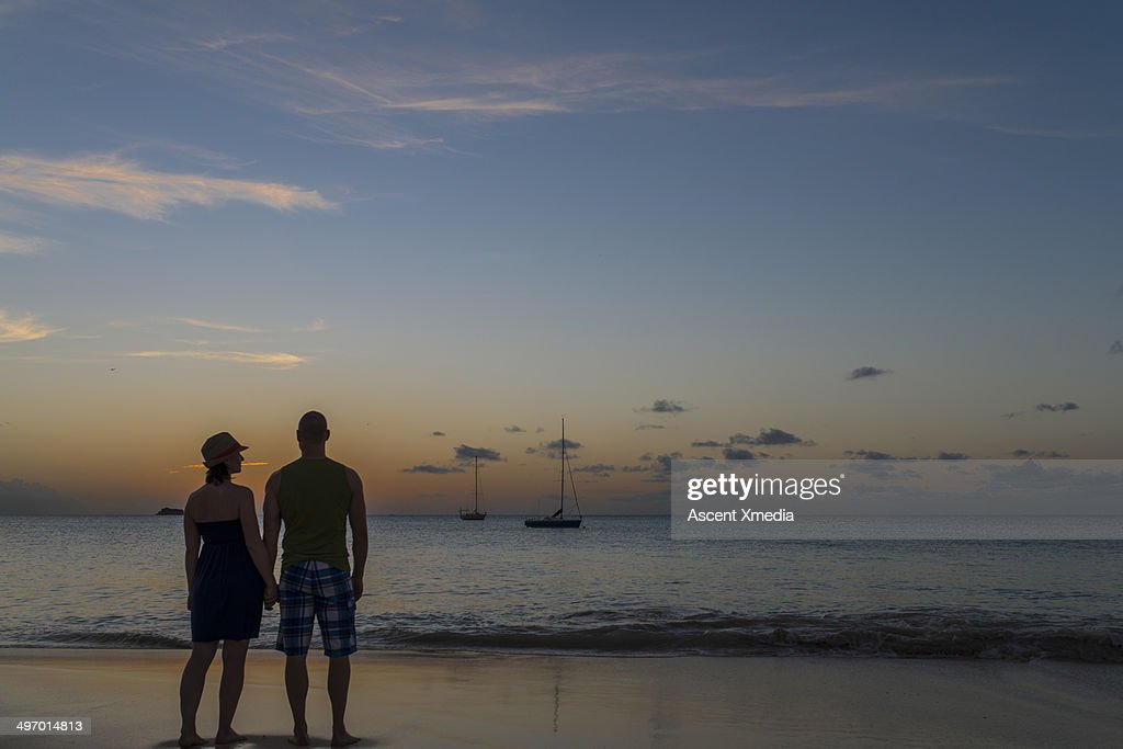 Couple look out across tranquil waters of lagoon