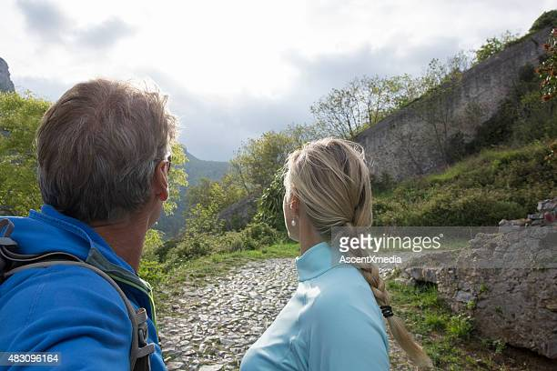 Couple look out at hillside in Liguria, Italy.