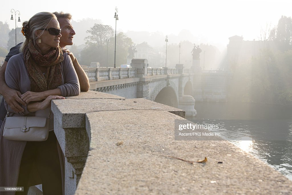 Couple look out to river from marble railing : Stock Photo