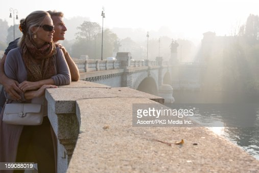 Couple look out to river from marble railing : Photo