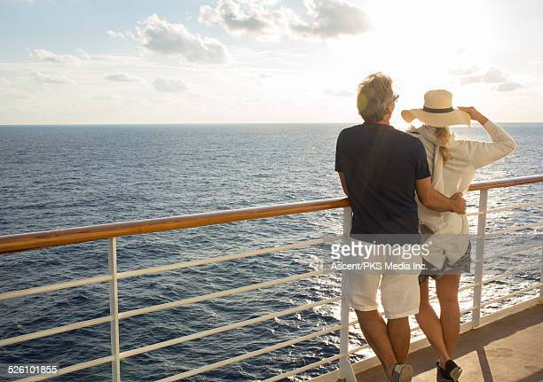 Couple look out to sea from boat railing