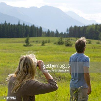 Couple look through binoculars in mountain meadow : Stock Photo