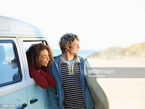 Couple looking along beach from camper van.