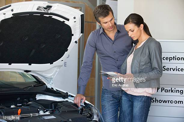 Couple looking at a car catalog in showroom