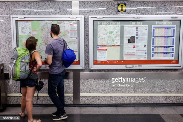 A couple looking at a subway map in Banco de Espana Metro Station