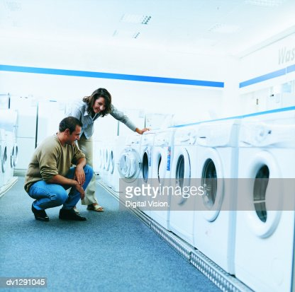 Couple Looking at a Washing Machine in An Aisle of a Department Store