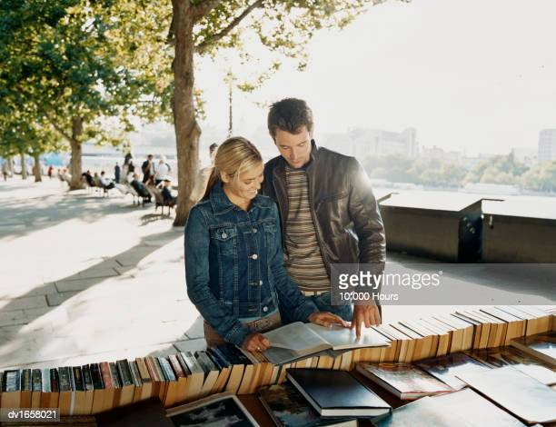 Couple Looking at an Open Book, with the Man Pointing at a page, at a Market Stall, London