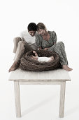 Couple looking at baby girl (2-5 months) lying in bird's nest on wooden table against white background