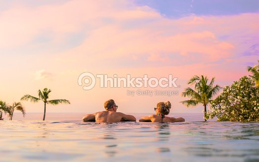 Couple looking at beautiful sunset in infinity pool : Stock Photo