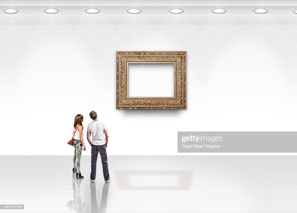 Couple looking at blank art with gold frame