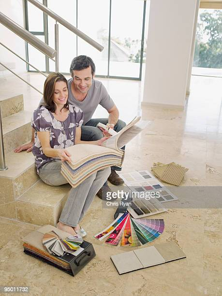 Couple looking at carpet samples on staircase in empty house