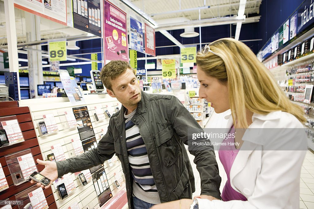 Couple looking at cell phones in electronics section of department store : Stock Photo