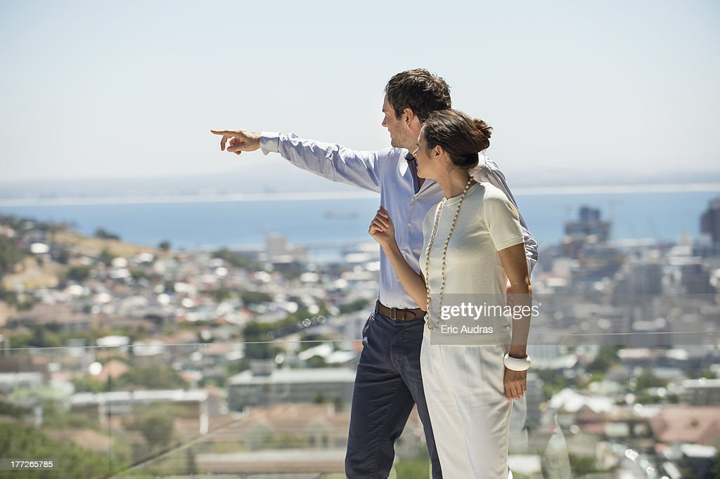 Couple looking at city view from a terrace : Stock Photo