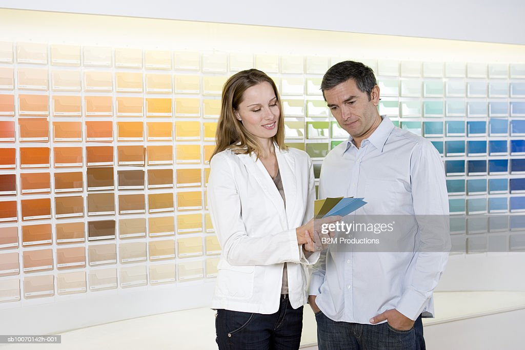 Couple looking at color swatches in hardware shop : Stock Photo