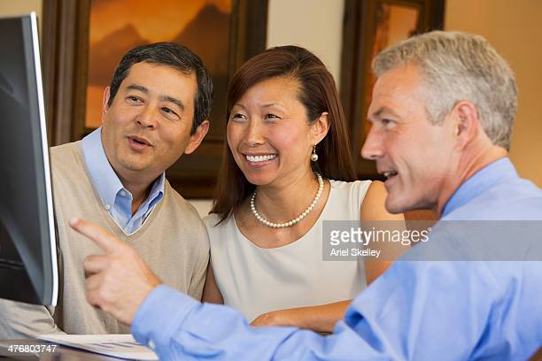 Couple looking at computer with their financial advisor