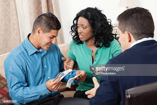 Couple à la recherche à la carte de crédit avec le Conseiller financier factures