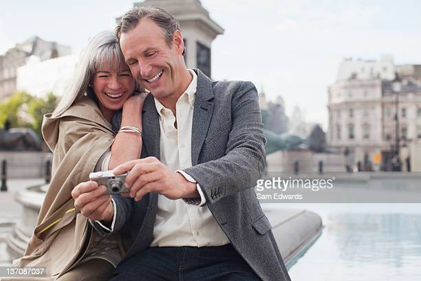 Couple looking at digital camera along Thames river in London