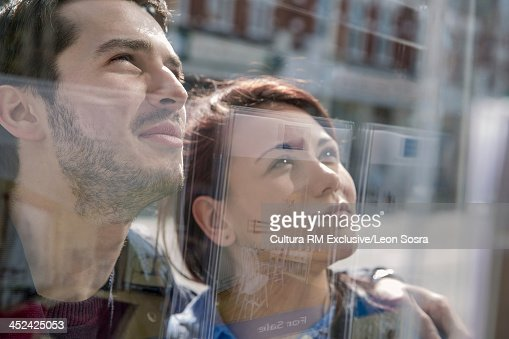 Couple looking at display of advertisements in estate agent window : Stock Photo