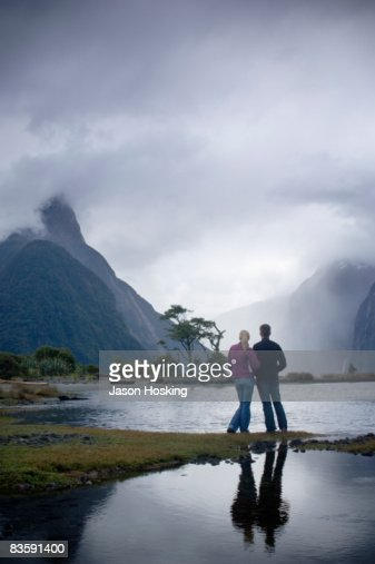 Couple looking at dramatic, stormy mountain : Stock Photo
