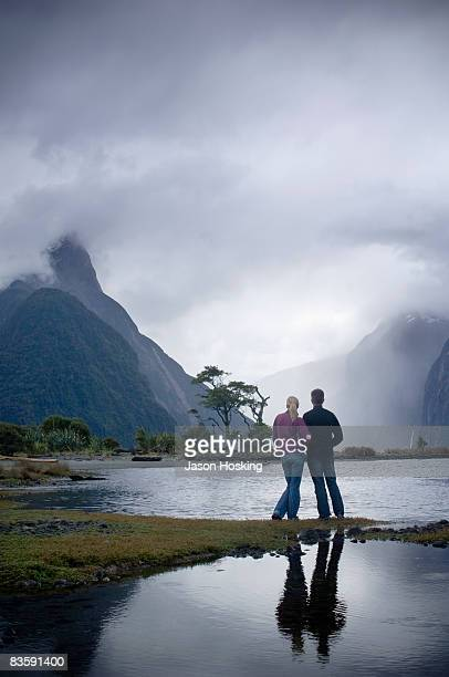 Couple looking at dramatic, stormy mountain