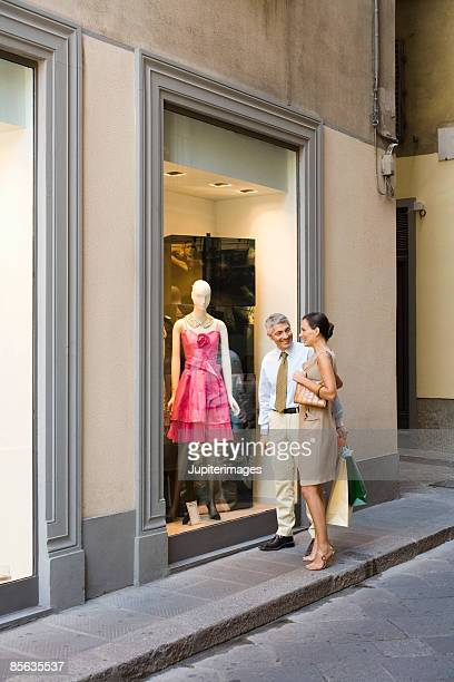 Couple looking at dress in store window, Florence, Italy