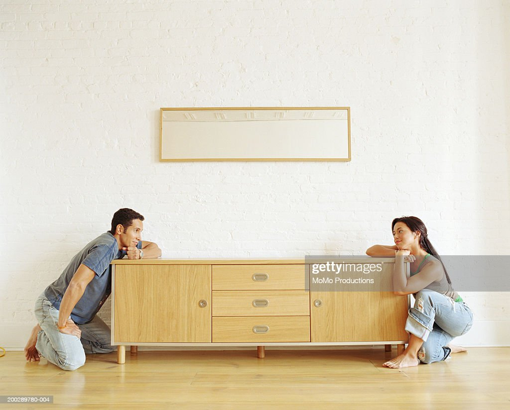 Couple looking at each other across cabinet top, side view : Stock Photo