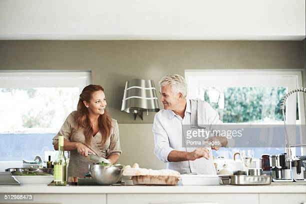 Couple looking at each other while preparing food