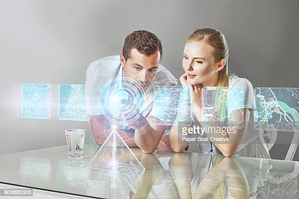 Couple looking at hologram projection of maps