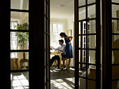 Couple looking at laptop monitor,view through French doors