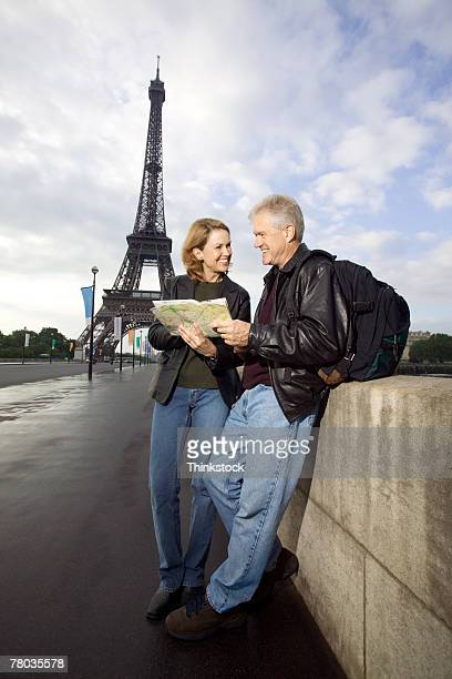 Couple looking at map by Eiffel Tower, Paris
