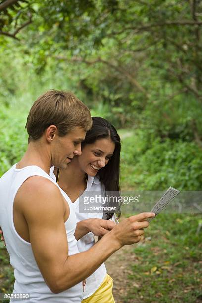 Couple looking at map in forest, Islas del Rosario, Colombia