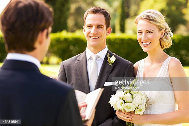 Couple Looking At Minister During Wedding Ceremony