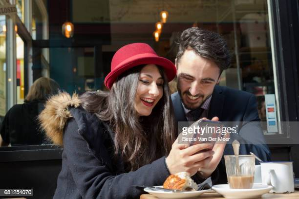 Couple looking at mobilephone sitting in cafe, having coffee.