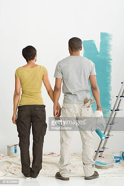 Couple looking at paint on wall