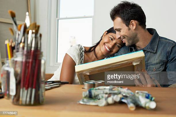 Couple Looking at Painting in Studio
