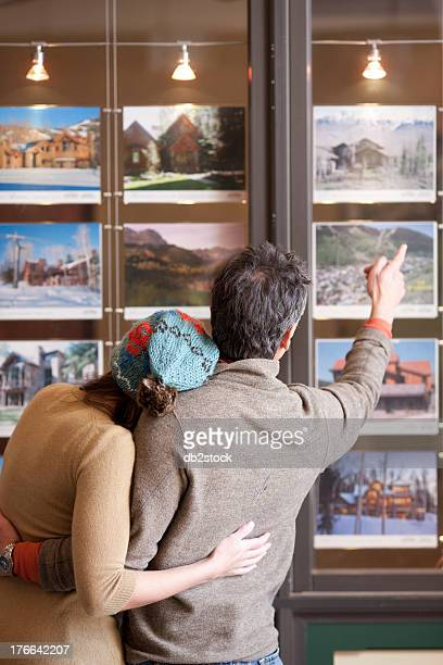 Couple looking at photographs in travel agents window, rear view