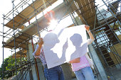 Couple looking at plans on building site