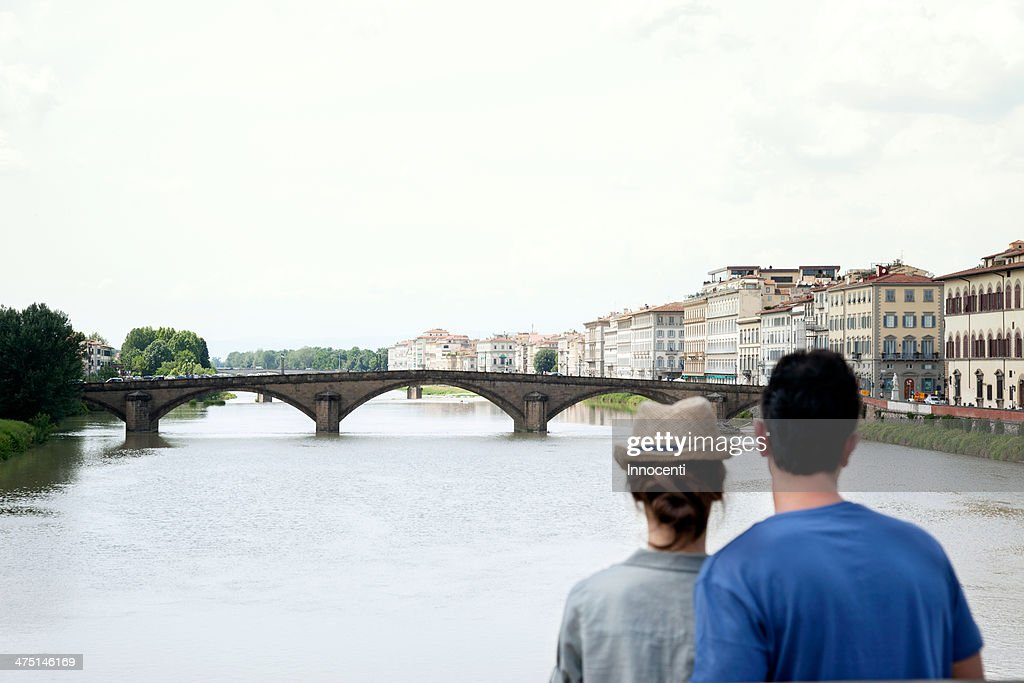 Couple looking at Ponte alle Grazie, Florence, Tuscany, Italy